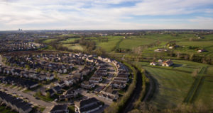 """photo graph of a """"Smart Growth Boundary"""" in Kentucky. Image shows housing development abutting farmland that is protected by the boundary."""