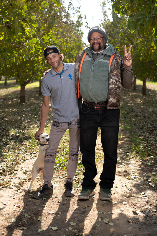 Father and Son farmers side hug and smile in their nut production orchard.