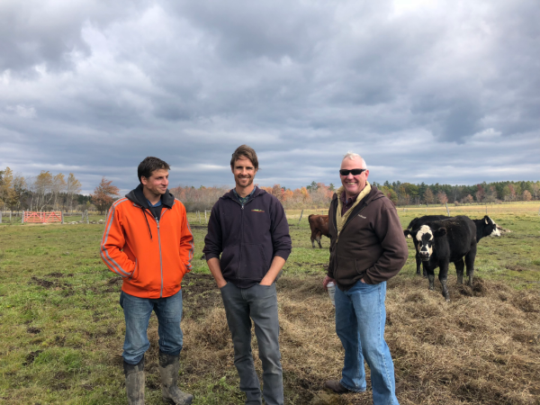 Tim Biello and farmers stand in pasture